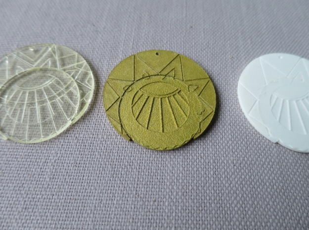 "Estaban and Zia's Medallion from The Mysterious Ci 3d printed In ""Transparent Detail"", A painted one (is ""Aluminide"" underneath), and one in ""White, Strong and Flexible"" which is the recommended material for painting."