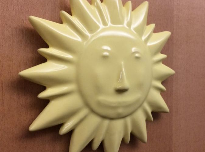 Picture of yellow ceramic sun mounted to door.