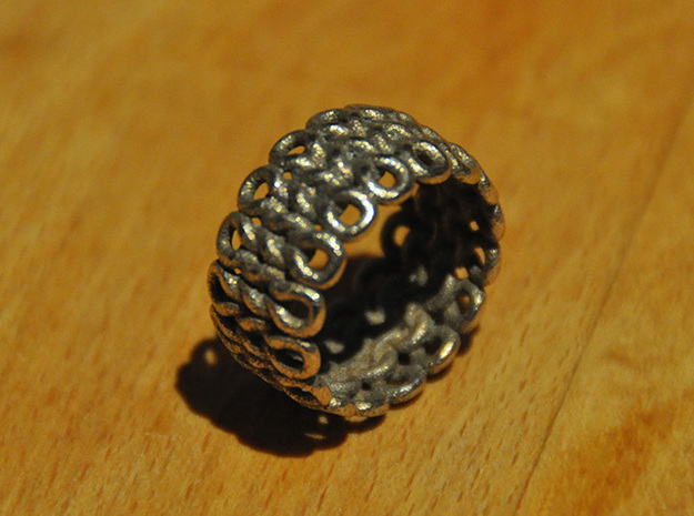 Knitter's Ring (59mm) 3d printed The ring in stainless steel.  This model came from Shapeways with a bit of residue stuck in the cracks between stitches.  I removed the excess material with a needle.