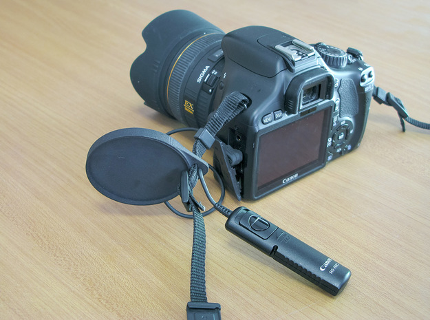 Holder for the camera lens cap . in Black Natural Versatile Plastic