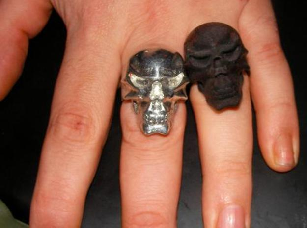 Skull Ring 3d printed The original and the pewter rings together. Because of the shrinking of the metal as it cools it now fits onto a larger finger.