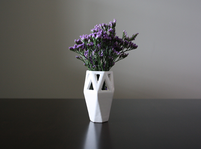A petite angular vase.  Its geometric lines contrast and compliment it's inhabitants.