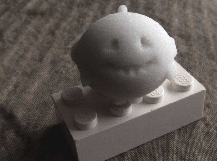 Bubbie's Little Guy 3d printed in sandstone, on a Lego brick to show scale