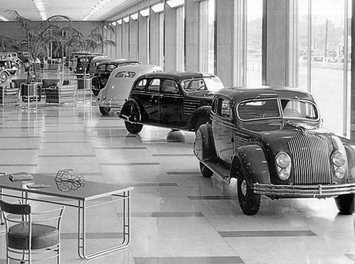 "1934 Chrysler Airflow Dealer Promo 16"" Frame model 3d printed 1934 Chrysler showroom. A miniature frame model sits on the table in the foreground."