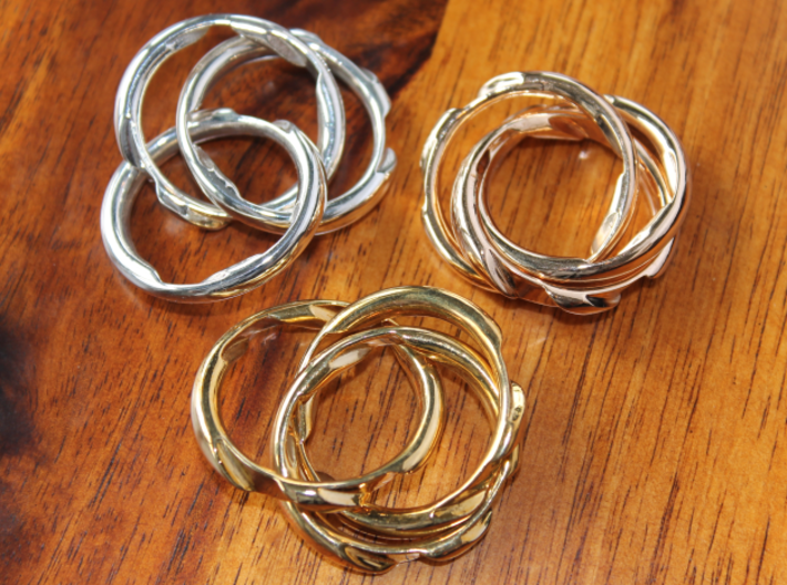 Three Phase Puzzle Ring 3d printed Interlocking Silver, Bronze, and Brass in the scrambled state.