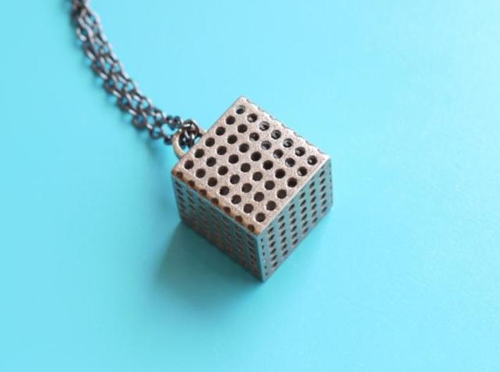 Perforated Cube Pendant 3d printed steel perforated cube on blue background
