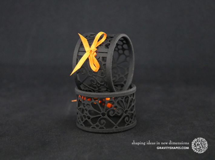 A large napkin ring with Mosaic-3b 3d printed The photo shows prints made of black strong and flexible incl. orange lacing.