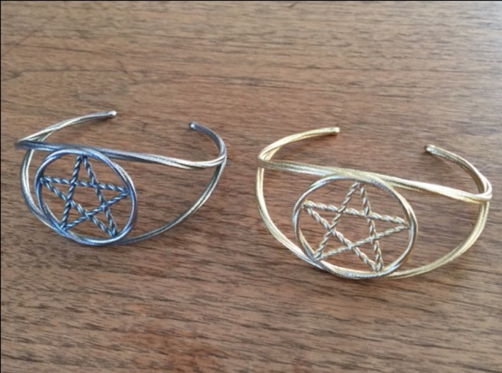 Woven Pentacle cuff/armband 3d printed The woven pentacle armband in two different materials. On the left is stainless steel; on the right is polished gold steel.