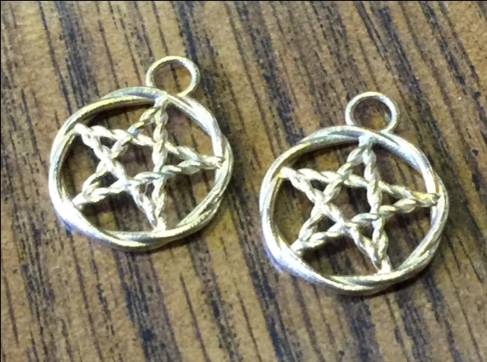 Woven pentacle earrings 3d printed The pair of woven pentacle earrings in raw brass.